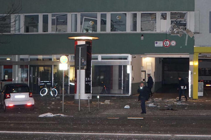 Die Trümmer liegen weit verstreut auf Gehweg und Straße. An den Fenstern (oben rechts) ist die Verwüstung zu sehen.