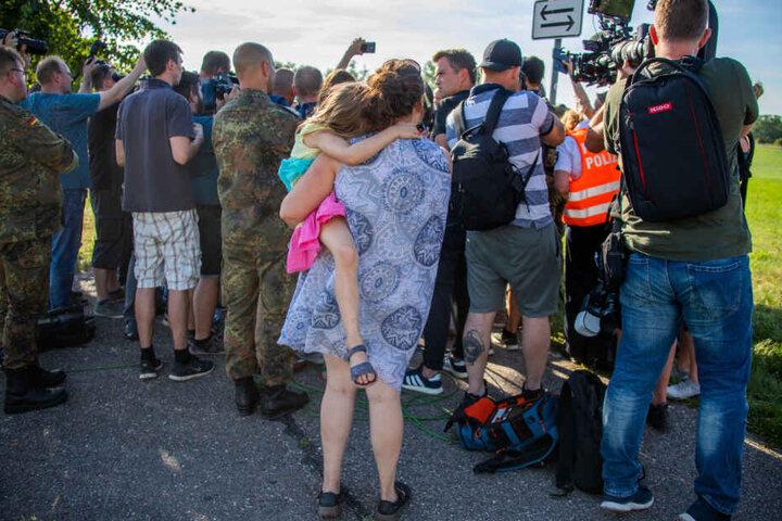 Eine Einwohnerin von Jabel mit einem Kind auf dem Arm verfolgt die Presseerklärung der Bundesverteidigungsministerin in der Nähe der Absturzstelle eines Eurofighters.