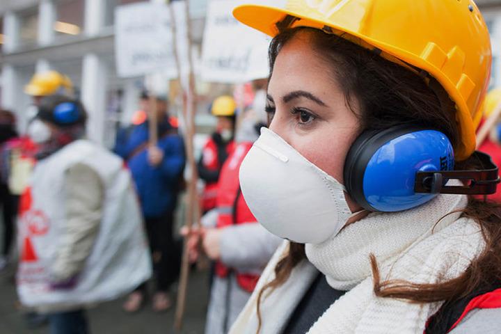 Eine Demonstrantin mit Bauhelm, Atem- und Ohrschutz protestiert gegen die Baumängel an den Schulen in Berlin.