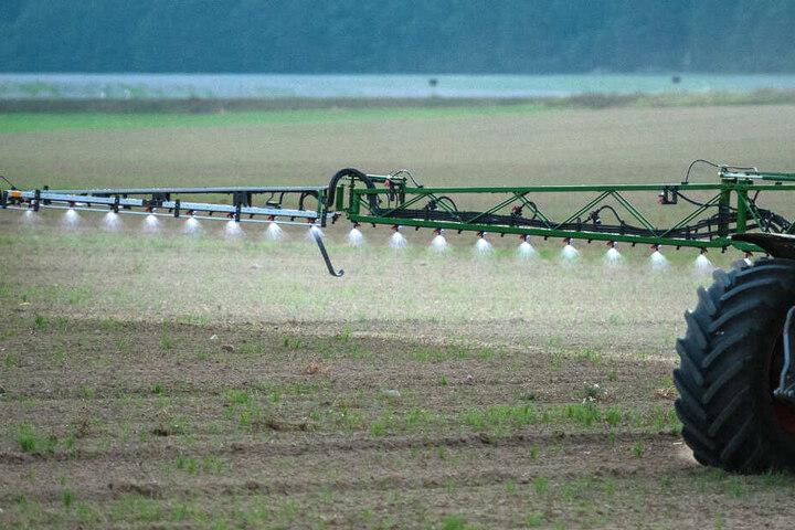 Ein Landwirt fährt mit einer Pestizid- und Düngerspritze über ein Feld.