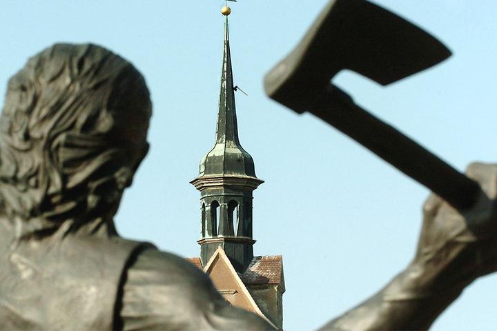 Diese Bronzefigur mit Beil in der Hand steht in Mockrehna. Im Hintergrund ist der Turm der Dorfkirche zu sehen.