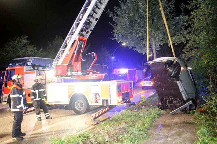 Mit einem Drehleiterwagen zog die Feuerwehr das Auto aus dem Graben und den Abhang hoch.