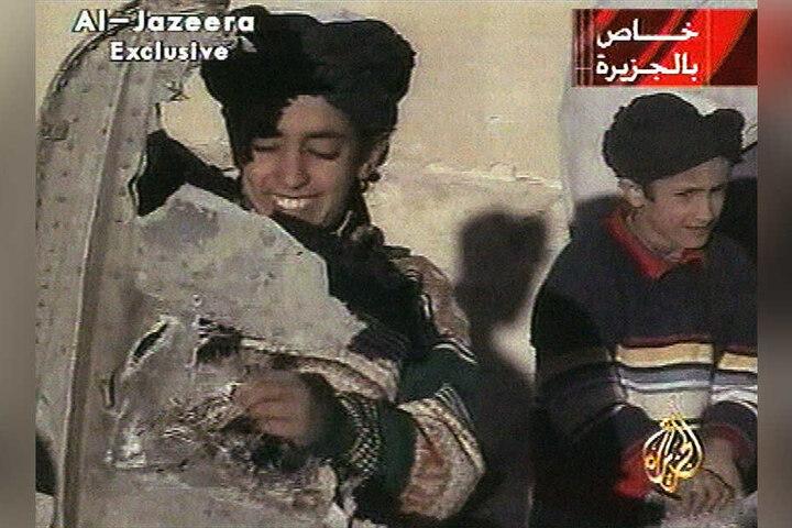 Ein Al-Jazeera-Video vom 07.11.2001 zeigt Hamsa bin Laden (l) in Ghazni (Afghanistan), der nach Angaben der Taliban Teile eines zerstörten US-Hubschraubers hält. Hamsa bin Laden war in terroristische Aktivitäten involviert.