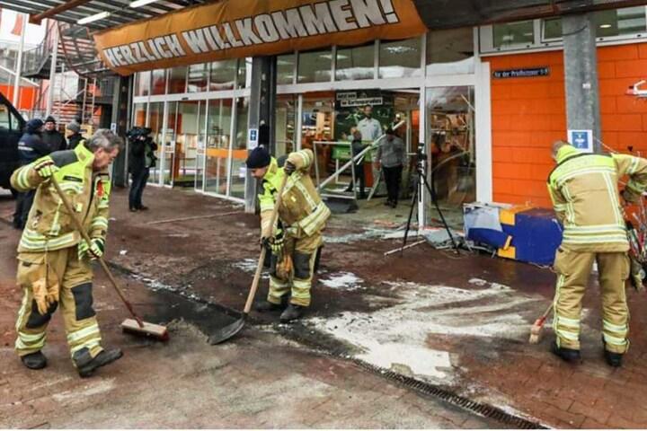 Feuerwehrmänner beseitigen die Brandspuren vor dem Baumarkt.