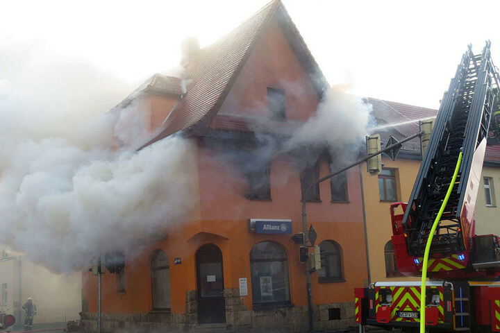 Die Feuerwehr löscht einen Hausbrand in Weimar (Thüringen). Flammen und dichte Rauchwolken schlagen aus den Fenstern des Eckhauses am Weimarer Stadtring.