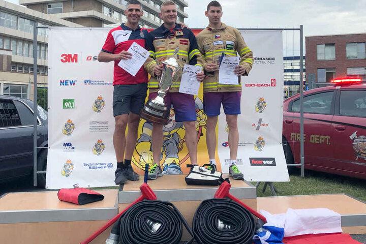 """Michael Brousil (M) aus Tschechien freut sich über den Titel """"härtester Feuerwehrmann"""", gefolgt von Marcin Zdzieblo (l) aus Polen und Pavel Kourik (r) aus Tschechien."""