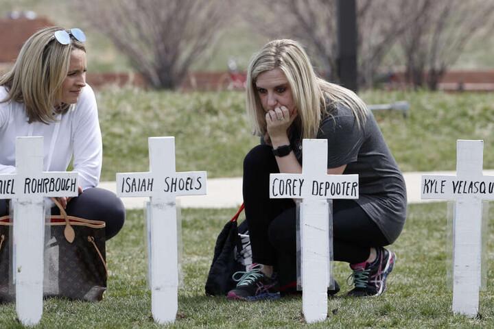 Cassandra Sandusky (r), Absolventin der Columbine High School, und ihre Freundin Jennifer Dunmore knien neben Kreuzen mit den Namen der Opfer des Attentats an der Columbine High School.