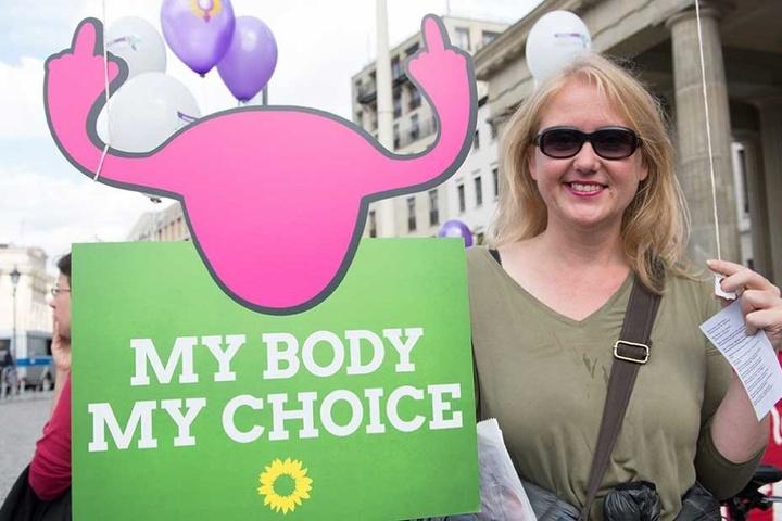 """""""Mein Körper. Meine Wahl"""" steht auf englisch auf diesem Plakat einer Abtreibungsbefürworterin."""