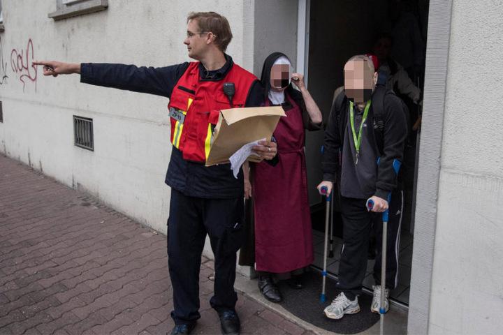 Ein Mitarbeiter der Feuerwehr koordiniert die Evakuierung von gehbehinderten Menschen in Frankfurt.