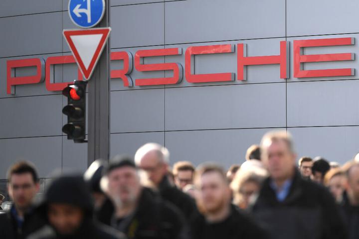 Mitarbeiter von Porsche stehen vor dem Stammsitz des Autobauers in Stuttgart.