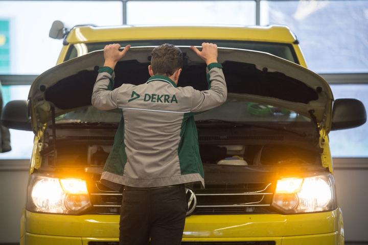 Ein Mitarbeiter der Prüforganisation Dekra öffnet im Rahmen einer Hautuntersuchung (HU) die Motorhaube eines VW T5 Diesel. (Symbolbild)