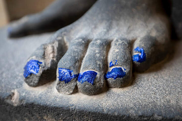 Unbekannte bemalten die Fußnägel der beiden Figuren mit blauem Lack. Auch die Kirchentür bekam Farbe ab.