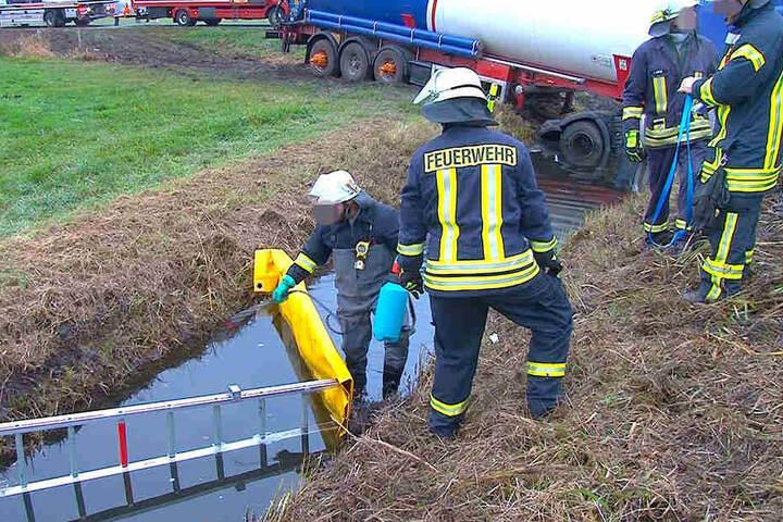 Die Kameraden der Feuerwehr legen den Wassergraben um den verunglückten Sattelzug trocken. Das Fahrzeug steckt tief im Boden fest.