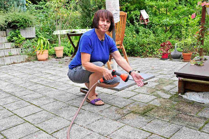 Mit dem Gartenschlauch bekommt Margitta Ost (67) die schwarzen Flecken auf  der Terrasse nicht weg. Die Anwohnerin braucht Hochdruckreiniger.