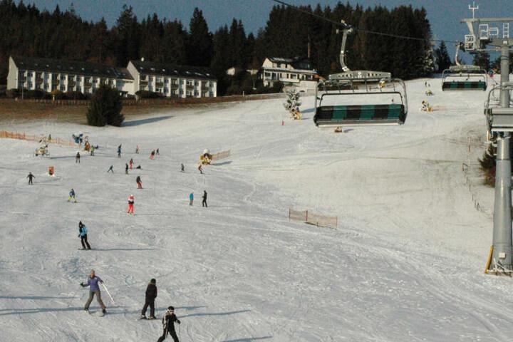 Skifahrer gleiten neben einem Sessellift einen Hang im Skigebiet Willingen hinunter.