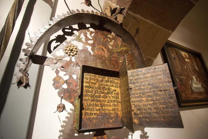 Eine Art Buch am schmiedeeisernen Grabkreuz erzählt vom Leben des  Verstorbenen. Eines von 70 Ausstellungsstücken.
