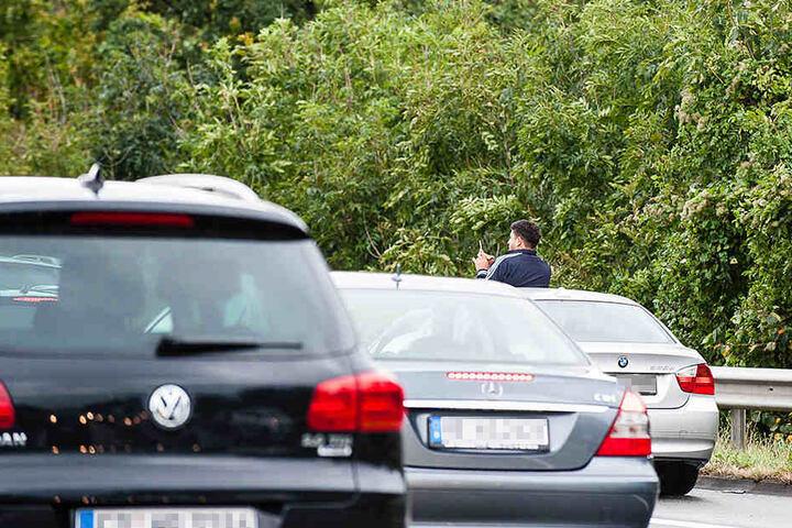 Ein Mann stellte sich in sein Auto, um aus dem Schiebedach Fotos zu machen.