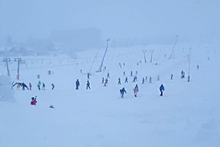 Trotz des Wetters sind einige Skifahrer auf dem Fichtelberg unterwegs.