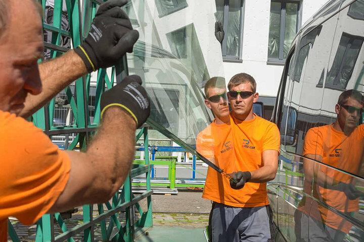 Die Arbeiter mit einer der schweren Glasscheiben.