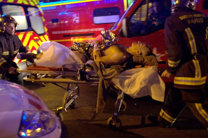 Ein Opfer der Terroranschläge von Paris auf einer Trage vor dem Bataclan Theater in Paris (Frankreich) am 13.11.2015.