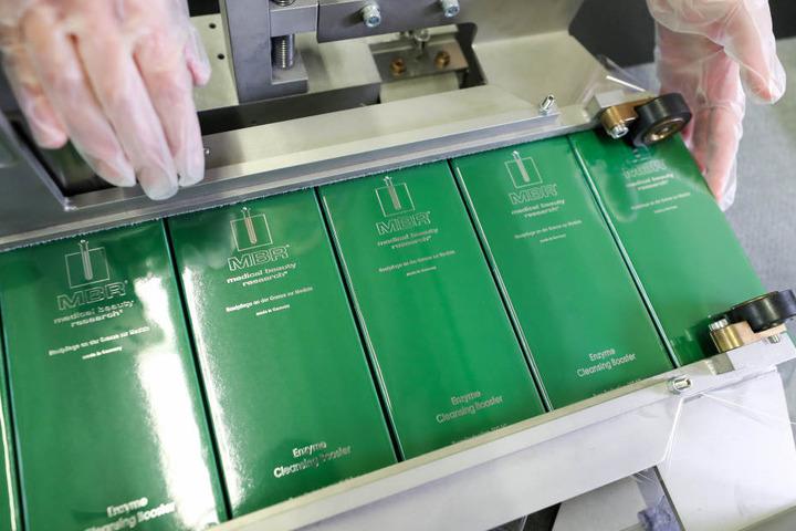 """Eine Mitarbeiterin der Medical Beauty Research GmbH (MBR) verpackt Kosmetikartikel aus der """"The Best""""-Kollektion."""
