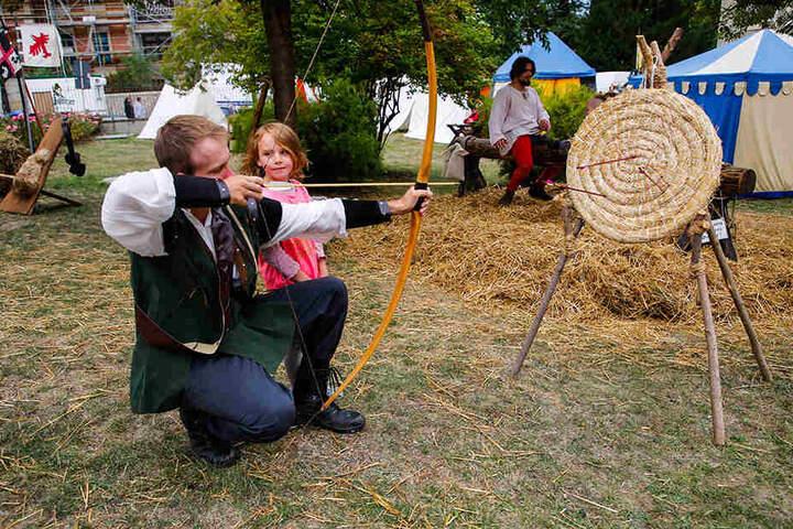 Ganz schön straff: Die kleine Evelin (6) lernt von Schütze Petr (28) aus Pilsen, wie man mit einer großen Armbrust umgeht.