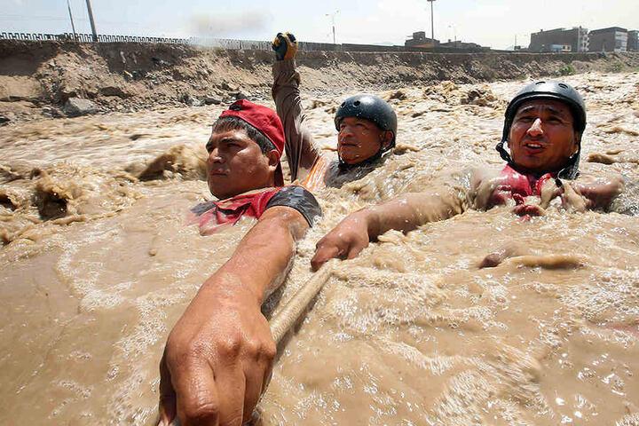 Reservisten der peruanischen Armee und bei Rettungsarbeiten in einem überschwemmten Fluss.