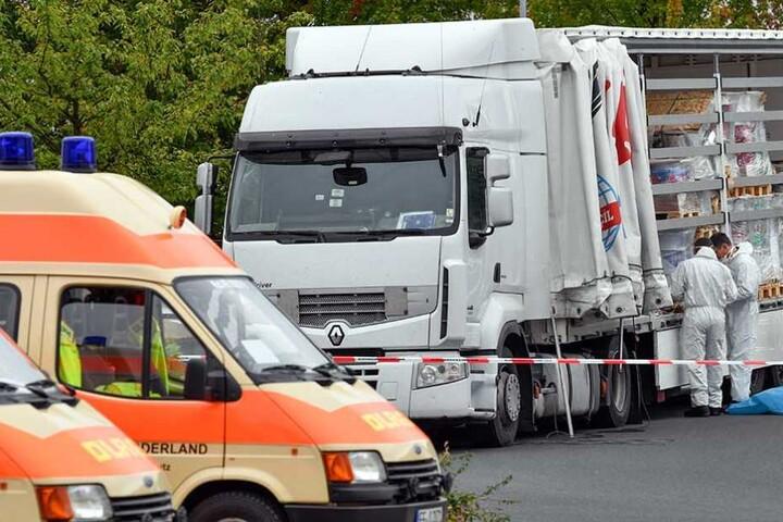 Ermittler stehen an dem Laster, in dem 51 Menschen zwischen der Ladung versteckt waren.