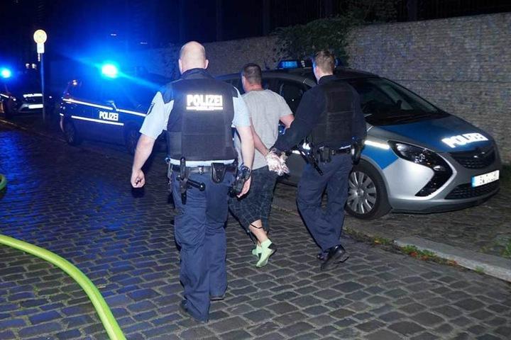 Polizisten führen den Verhafteten ab und bringen ihn zum Auto.
