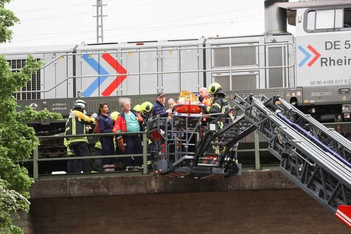 Rettungskräfte bei der Bergung des Tatverdächtigen an einer Bahnstrecke.