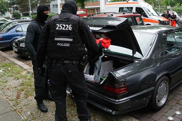 Fahnder durchsuchen den Kofferraum eines Mercedes der zu einem Tatverdächtigen gehört.