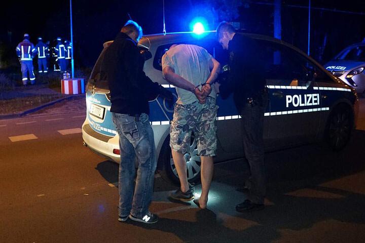 Der per Haftbefehl gesuchte Fahrer wird von den Polizeibeamten abgeführt.