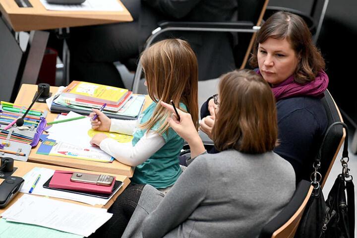 Neben Mutter und Kind sitzt die Abgeordnete Silke Gebel (Bündnis 90/Die Grünen, vorne).