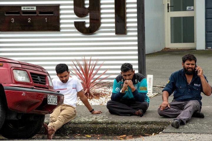 Trauernde Menschen sitzen nach den Schüssen in der Masjid Al Noor-Moschee auf der Straße.