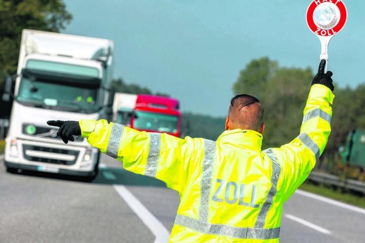 Ein Zöllner lotst einen Lkw von der Autobahn zur Kontrollstelle. Ein Großteil des illegal eingeführten Tabaks wurde in Lastwagen entdeckt.