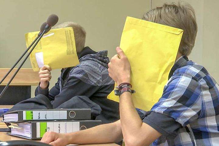 Zu Prozessbeginn versteckten zwei der drei Angeklagten ihre Gesichter hinter Heftern.