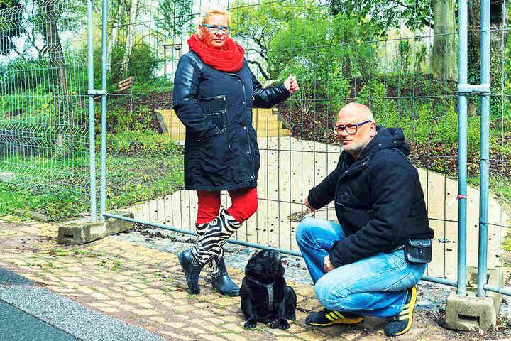 Ärgern sich über die lange Sperrung des Parks in Hellerau: Anwohner Lars (45)  und Yvonne Kühn (46) mit ihrem Mops Otto (6).