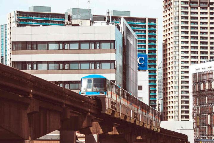 Eine Bahn fährt durch die Hochhausschluchten Tokios.