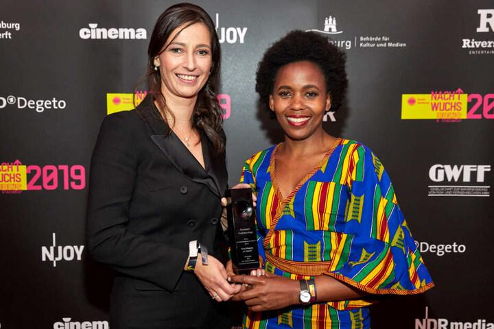 """Pinar Atalay (links), Fernsehmoderatorin und Laudatorin, steht neben der Gewinnerin in der Kategorie """"Beste Dokumentation"""", Beryl Magoko, die ihre Trophäe voller Stolz in der Hand hält."""