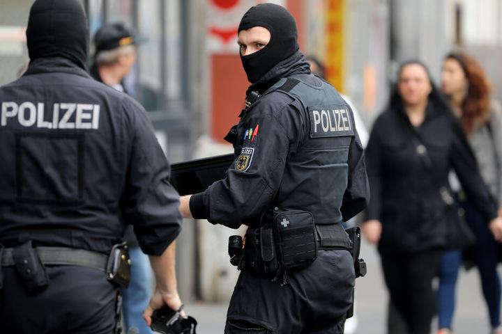Bundespolizisten gehen zu einem Wohnhaus in Köln.