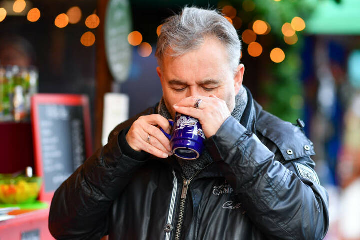 Lebensmittelkontrolleur Karl-Josef Leibig riecht auf dem Weihnachtsmarkt an einem Becher mit einer Glühweinprobe.