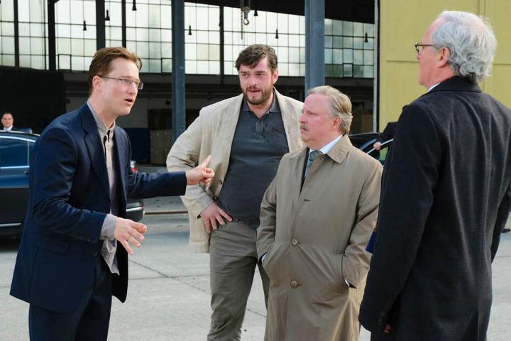 Martin Behrens (Zweiter von links; Ronald Zehrfeld) lauscht einer erregten Diskussion von Patrick Lemke (l., Alexander Fehling), Dr. Joachim Rauweiler (Axel Prahl) und Dr. Stefan Grünhagen (r., August Zirner).
