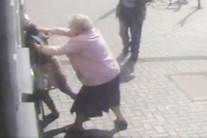 Als die junge Frau sich zwischen die Rentnerin und den Automaten stellt, wird sie sofort zurückgezerrt.