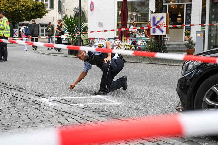 Ein Polizist markiert im abgesperrten Tatort auf dem Marienplatz einen Bereich. Nach Angaben der Polizei lag dort das Tatmesser.