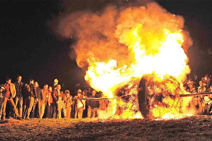 Die brennenden Räder rollen nahe am Publikum vorbei.