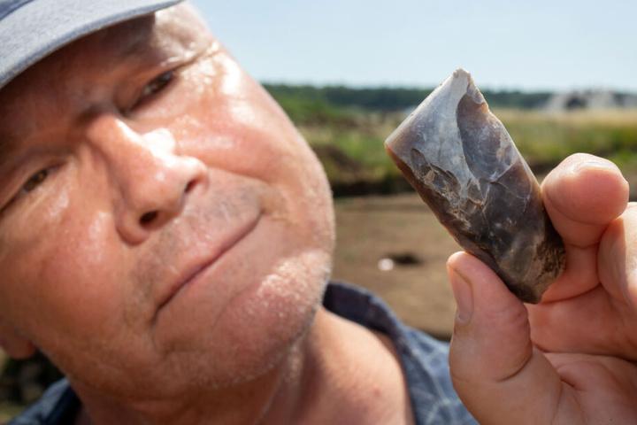 Archäologe Thomas Grasselt betrachtet ein geschliffenes Beil aus Feuerstein, dass in der Grabstätte gefunden wurde.