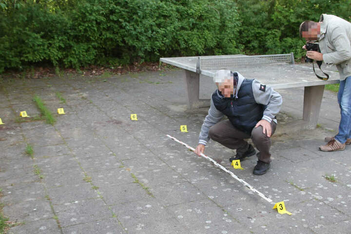 Zwei Polizeibeamte sichern Spuren an einem Spielplatz unweit des Fundortes des toten Säuglings.