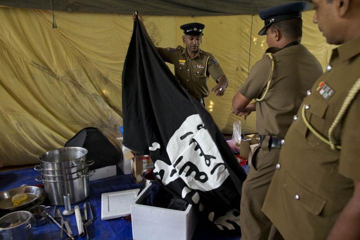 Polizisten zeigen das Schwarze Banner der Dschihadisten, das sie nach einer Anti-Terror-Razzia gefunden haben. (Archivbild)