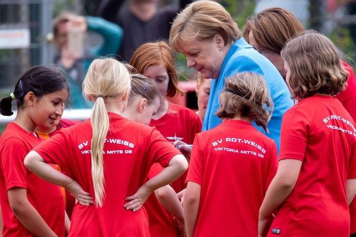 Kanzlerin Angela Merkel (63, CDU) signiert die Trikots der Fußballerinnen.