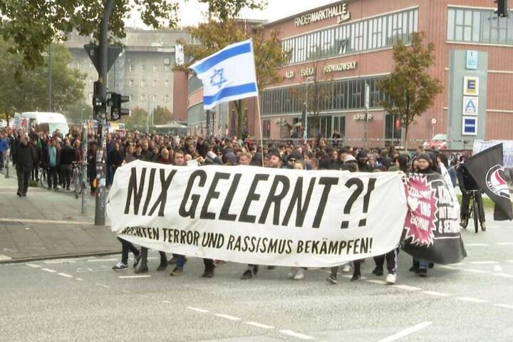 Mit Plakaten demonstrieren sie gegen rechten Terror.